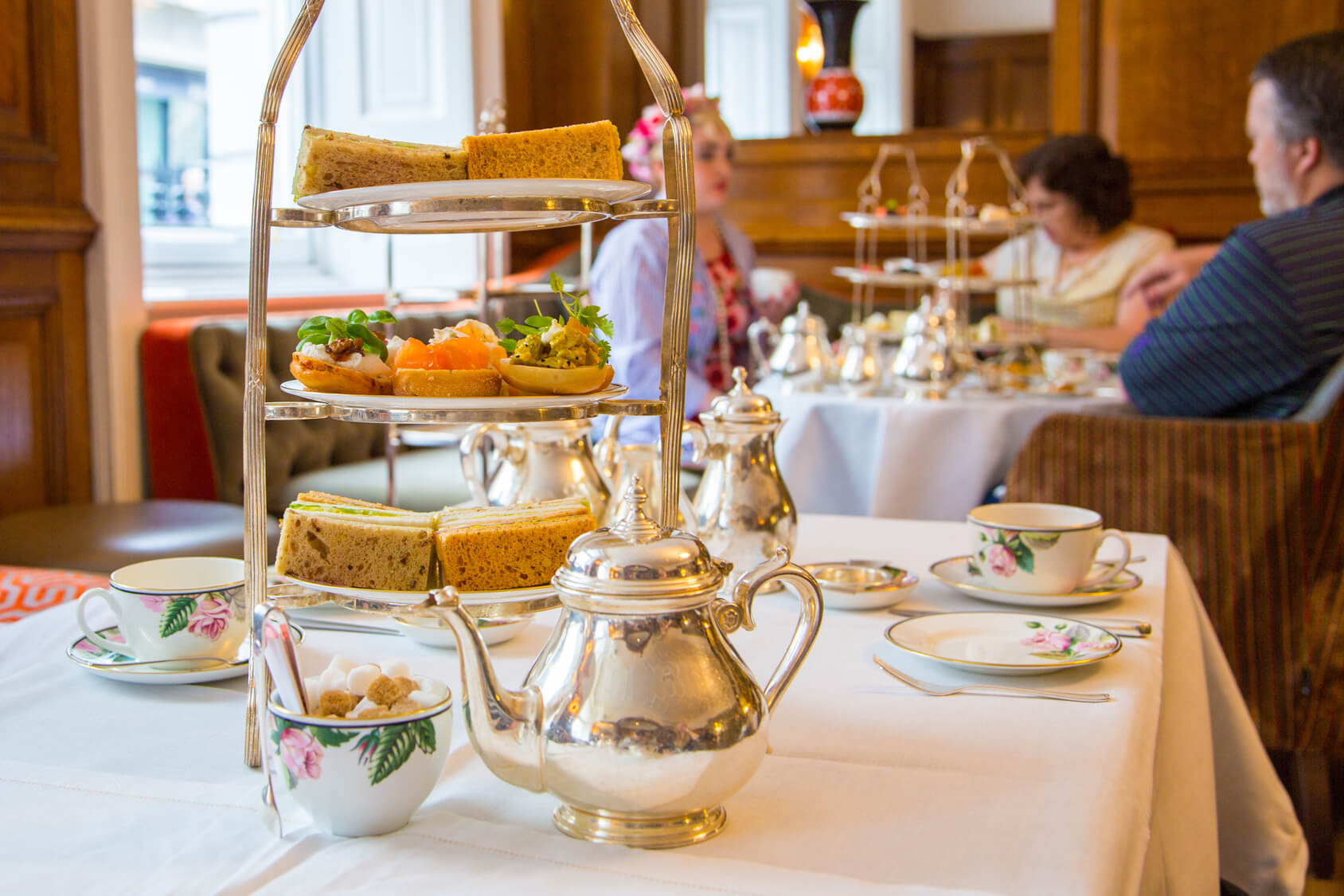 Afternoon tea with silver teapot and cake stand on a white line tablecloth