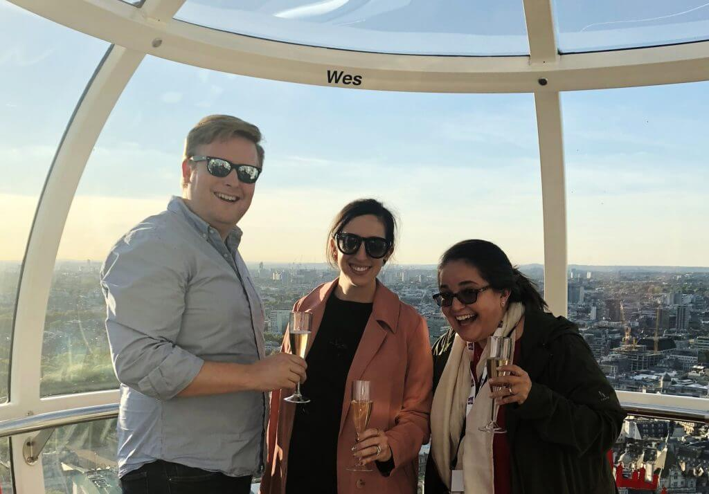 Three people enjoy Champagne on the London Eye during a corporate event