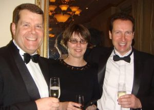 Three people at a corporate evening event with Champagne glasses in hand