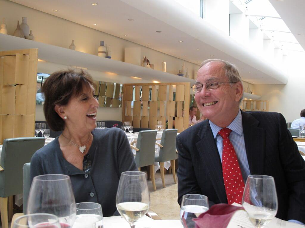 Middle-aged couple smiling as they enjoy a meal