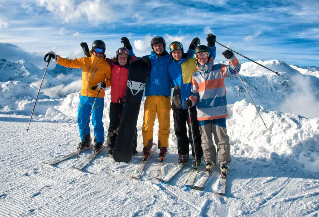 Group of 5 young men with skis on top of a mountain in the snow