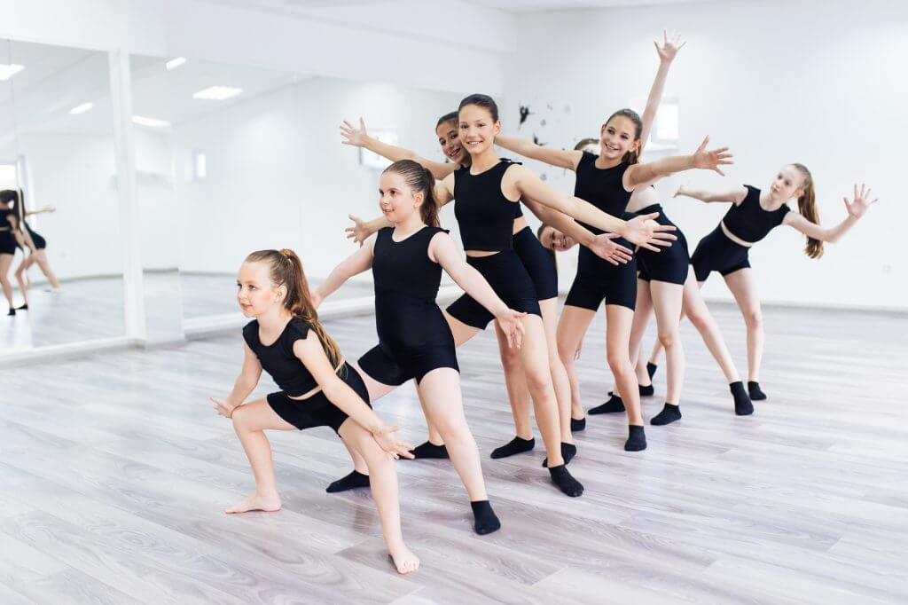 Group of girls dressed in black performing modern dance in a studio