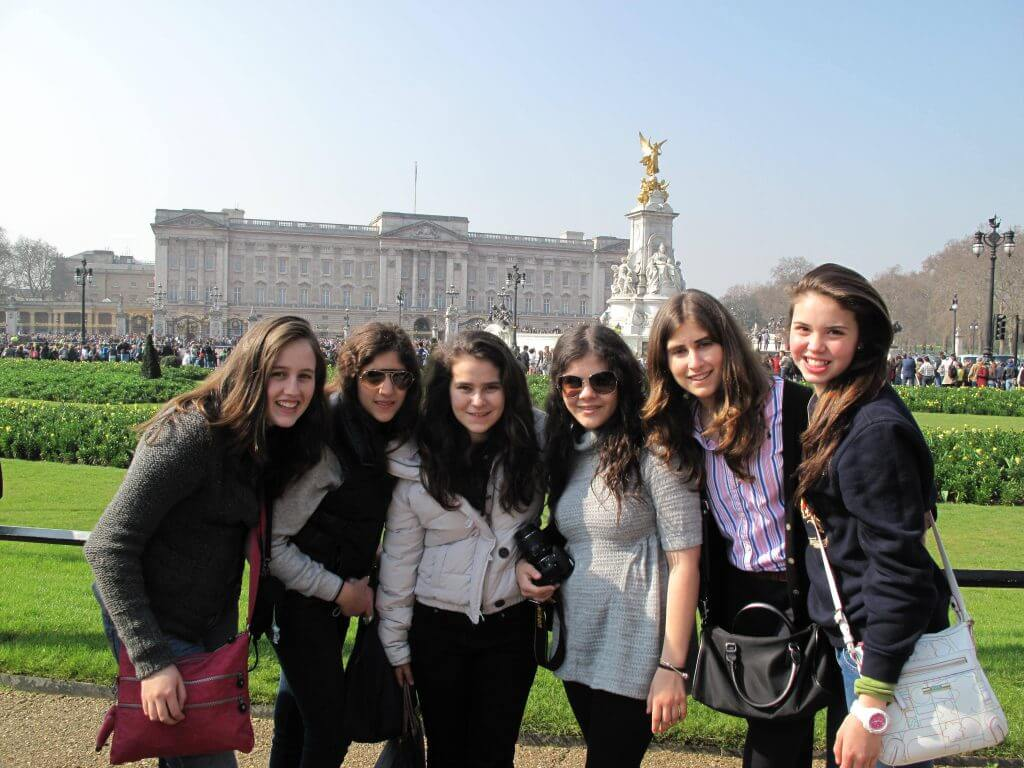 Group of 6 teenage girls on an educational tour in front of Buckinghams Palace
