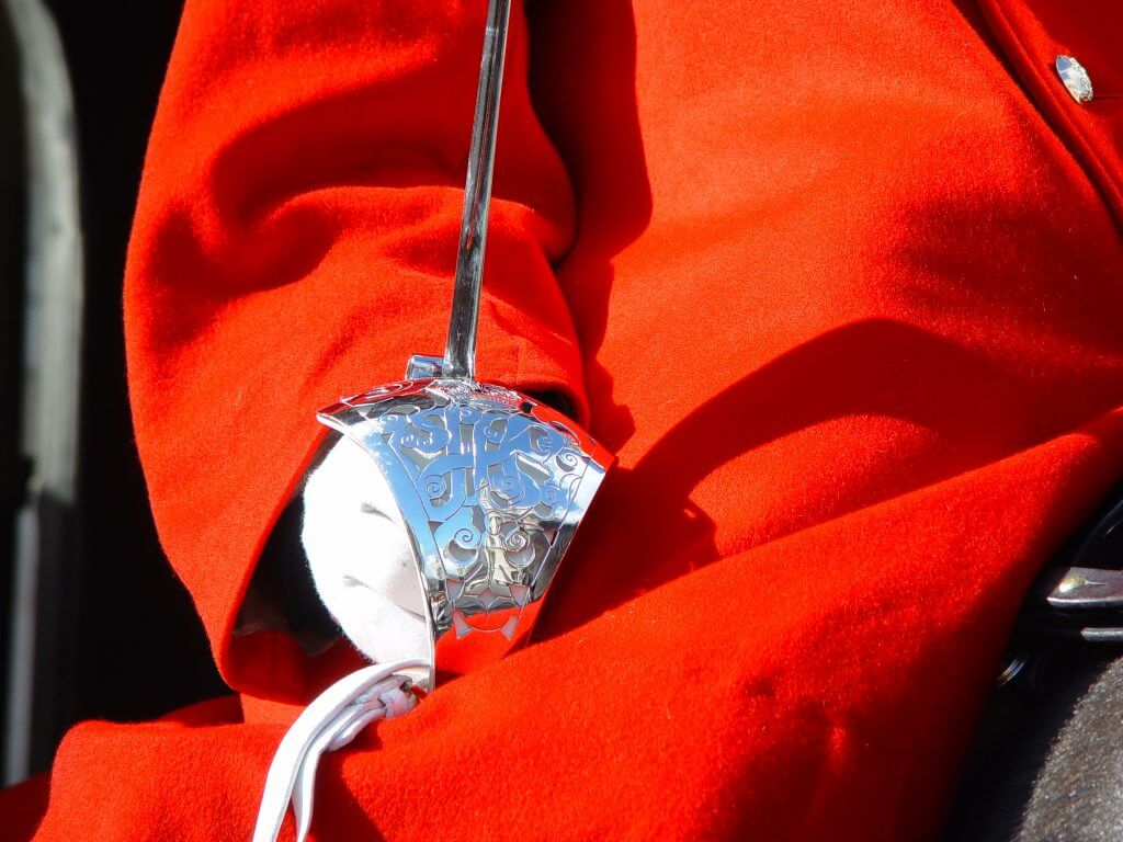 White gloved hand and silver sword against red coat of household cavalry guard