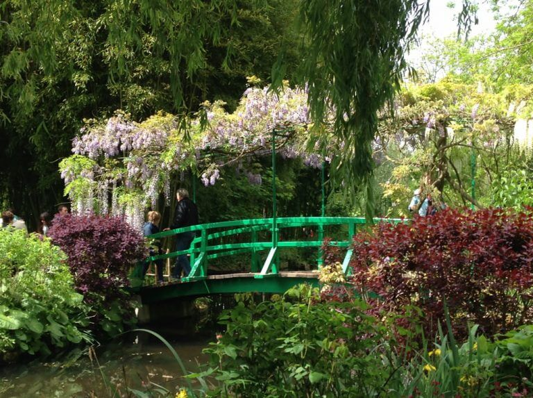 Green bridge over stream with wisteria in garden of Giverny