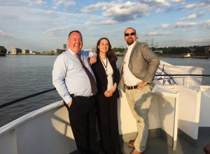 Three people enjoying a corporate evening event on a Thames river cruise