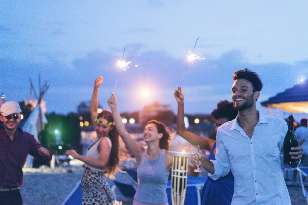Four happy people with sparklers at an incentive travel event