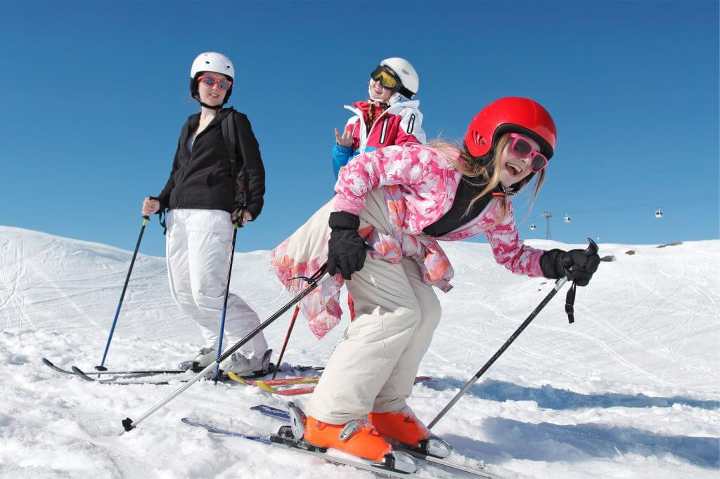 Three girls on a ski tour in the snow