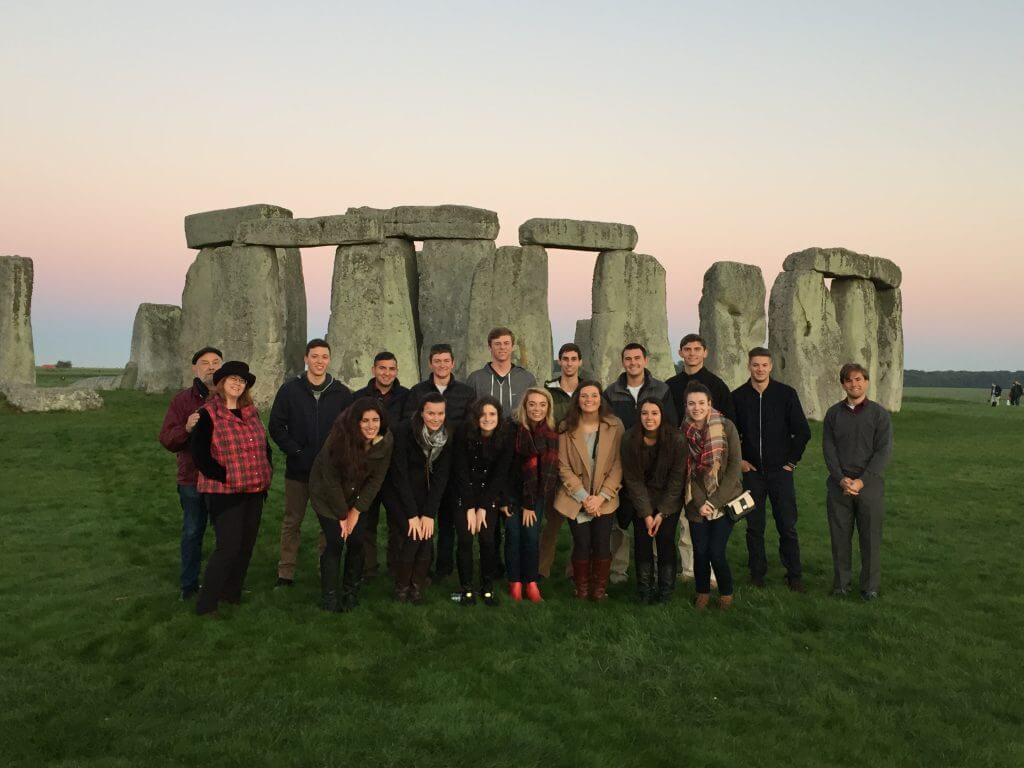 Group of students on educational with Stonehenge behind them