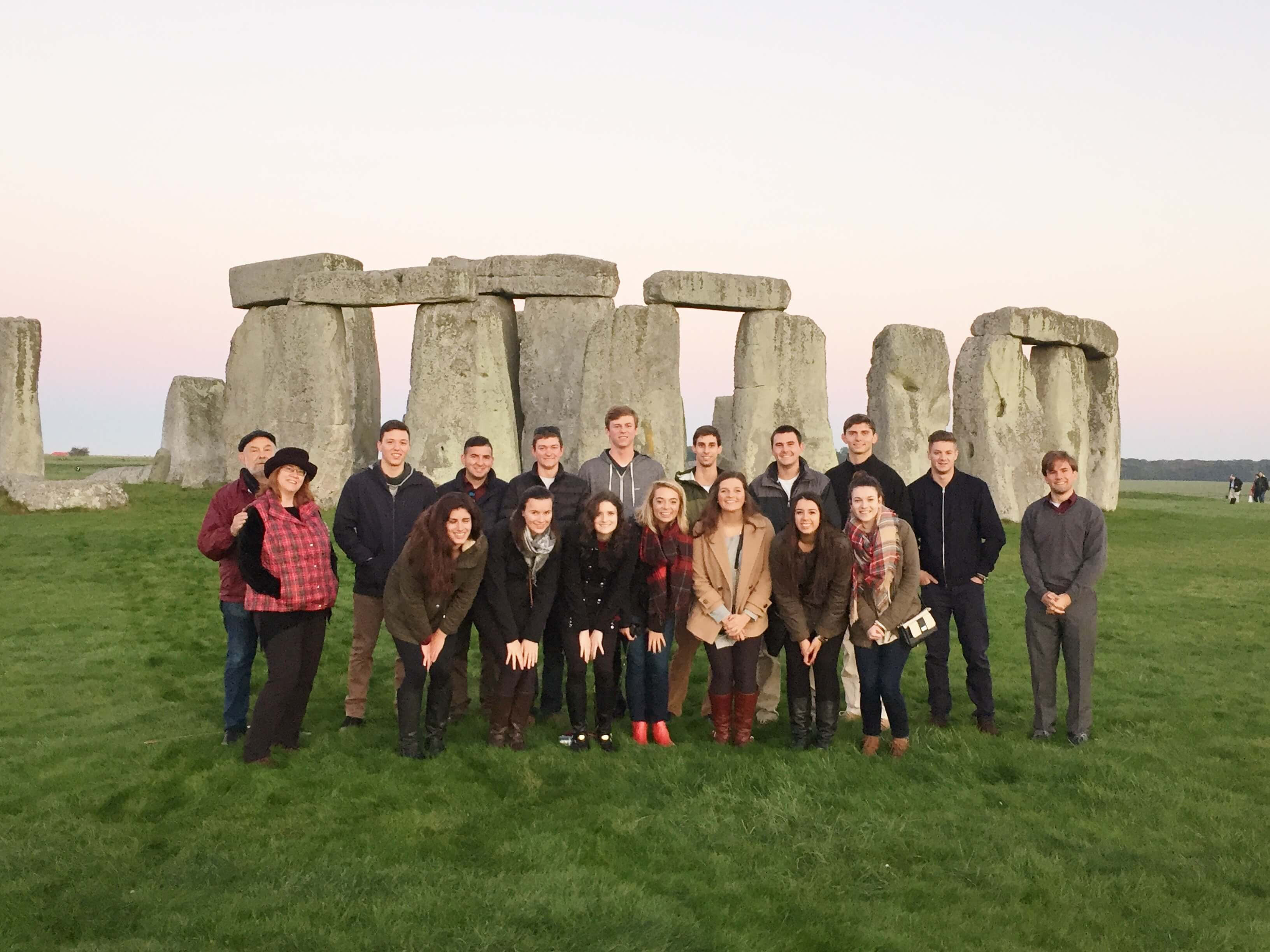 Group of University students on educational tour with Stonehenge at dawn behind them