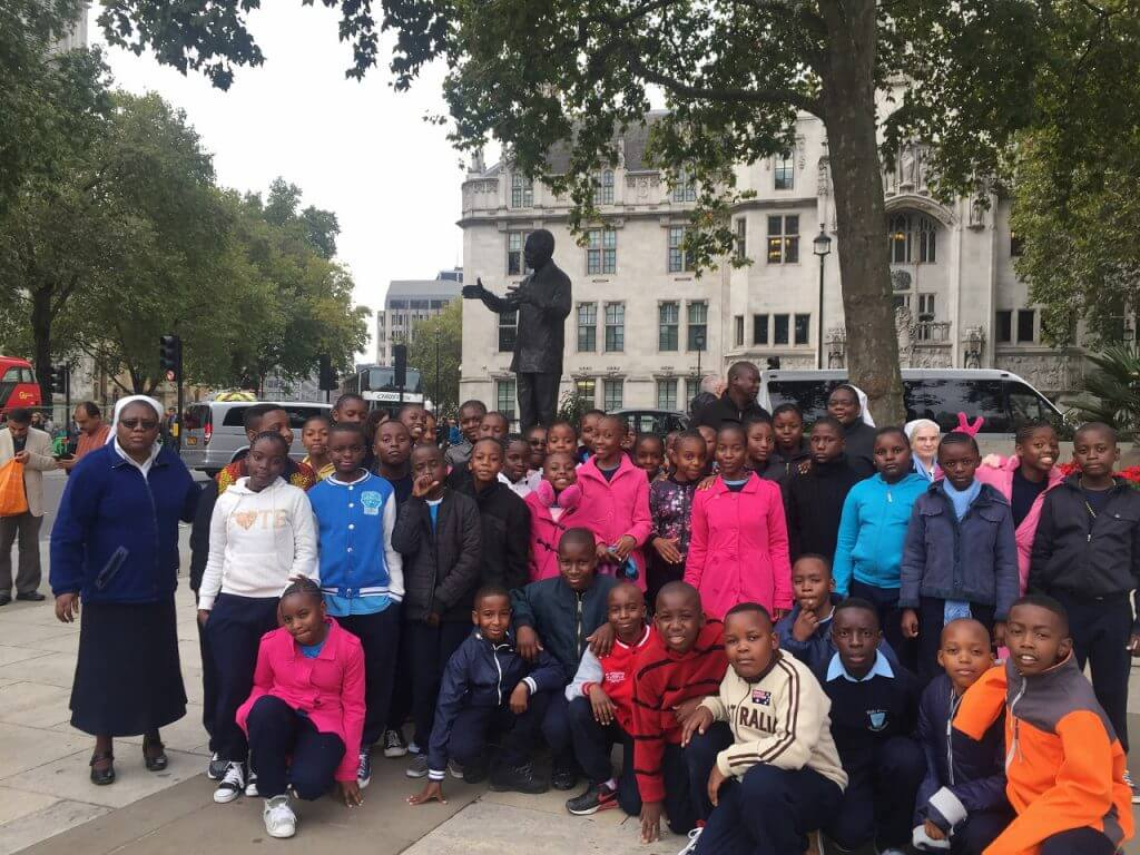 Group of African school children in front of statue of Nelson Mandela in Parliament Square
