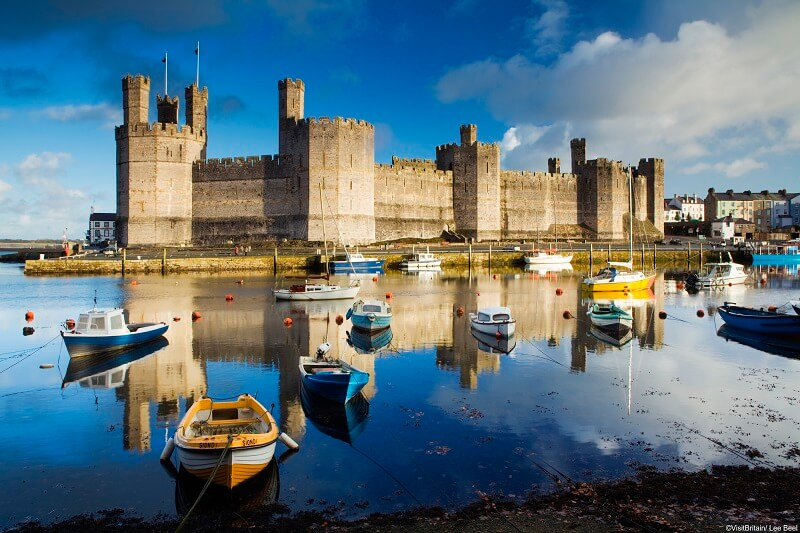 View of Caernarfon Castle and the Menai Straits with boats in the foreground